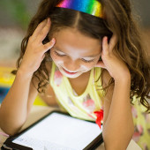 Young girl using an iPad - good broadband plans for families