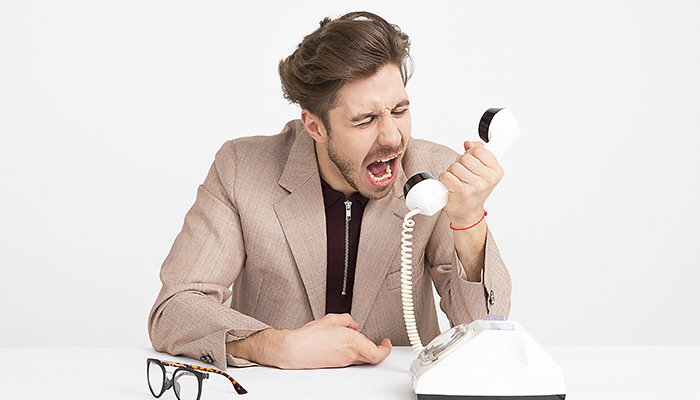 Frustrated man yelling into phone - Broadband provider top complaints